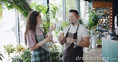 Frohe Kollegefloristen, die Holding plaudern und lachen, um Kaffee bei der Arbeit zu gehen stock footage