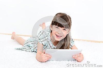 Frohes kleines Mädchen mit Apfel ipad