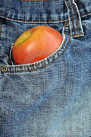 Front blue jeans pocket holding an apple