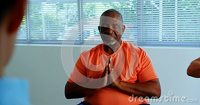 Front view of active African American senior man performing yoga in fitness studio 4k. Front view of active African American senior man performing yoga in stock video