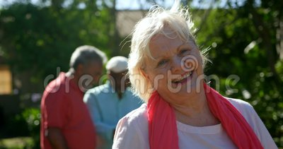 Front view of active Caucasian senior woman smiling in the garden of nursing home 4k. Front view of active Caucasian senior woman smiling in the garden of stock video footage