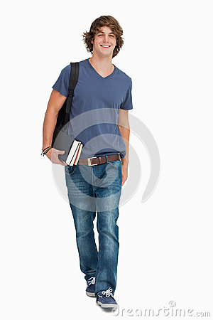 Front view of a male student walking with a backpack and books