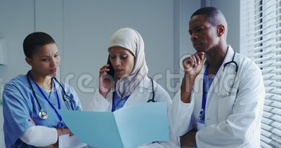 Front view of Middle-East female doctor talking on mobile phone with her colleagues in hospital. They are standing together and looking at medical file stock video