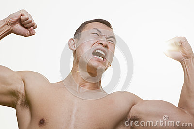Front view of shirtless, angry, roaring young man flexing his muscles with arms raised and looking away