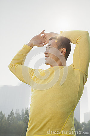 Front view of young, smiling, muscular man in a yellow shirt stretching, arms raised above his head in Beijing, China