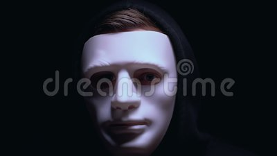 Fronte ferito nascondentesi dell'uomo nell'ambito della maschera, isolata su fondo nero, criminale archivi video