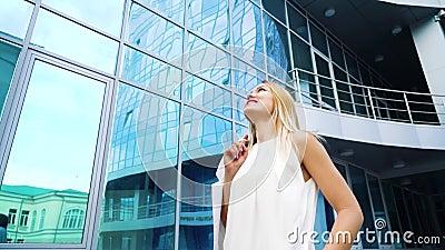 Froschperspektive von glücklichen Blondinen in der stilvollen Ausstattung, die durch Spiegeloberfläche des Wolkenkratzers übersch stock video