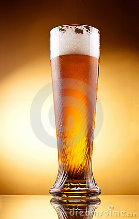 Frosty glass of light beer with froth
