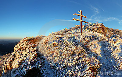 A frosty sunset in mountains with cross