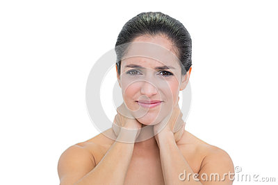 Frowning bare brunette touching her neck with both hands