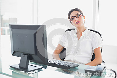 Frowning businesswoman sitting at her desk looking at computer
