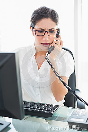 Frowning businesswoman sitting at her desk talking on the phone