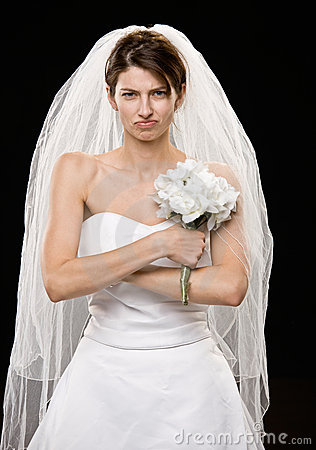 Frowning young bride in wedding dress and veil