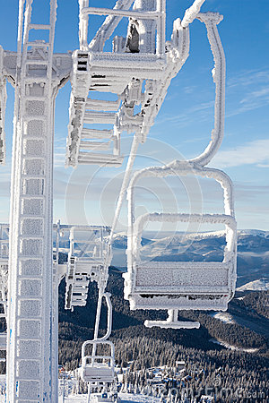 Frozen chair lift at snow resort in winter mountains on sunny da Stock Photo