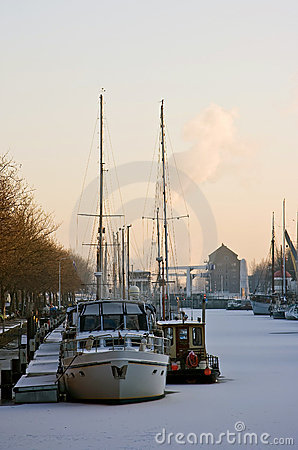 Frozen harbour with ships in winter at sunset