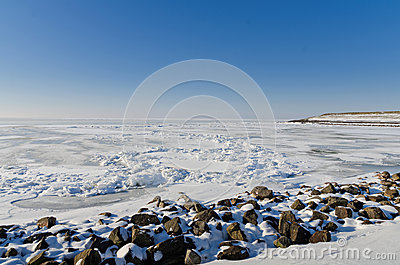 Frozen lake with crushed ice sheet and rocks