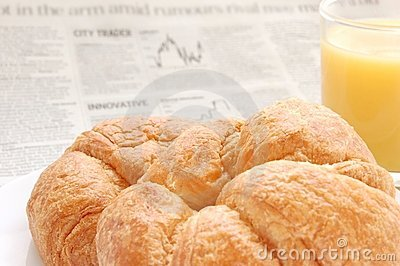 Fruit juice, croissant and business paper