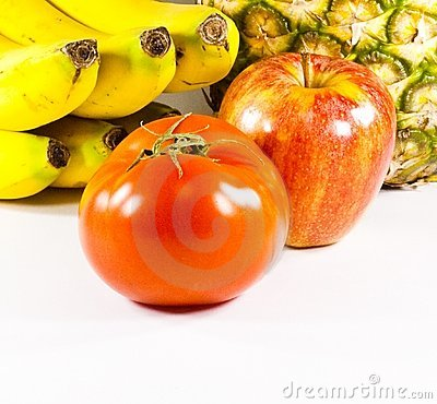 Fruits varied with tomato in first plane on white