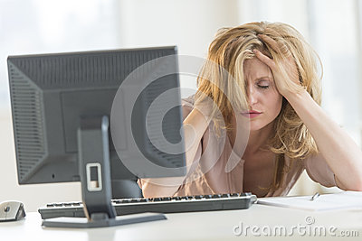 Frustrated Businesswoman With Hands In Hair Sitting At Desk