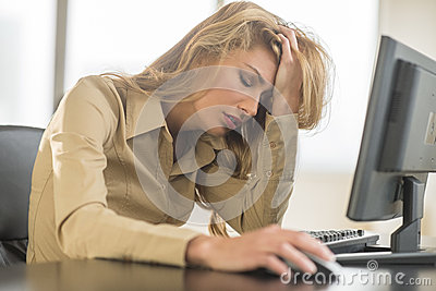 Frustrated Businesswoman Leaning On Computer Desk