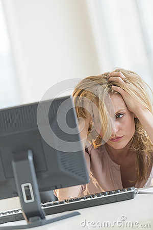 Frustrated Businesswoman Looking At Computer In Office