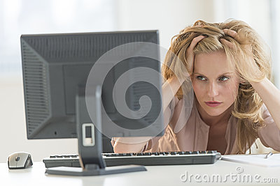 Frustrated Businesswoman Looking At Desktop PC In Office