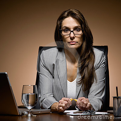 Frustrated businesswoman working late at desk