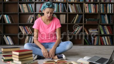 Frustrated student having a lot to read in library stock footage