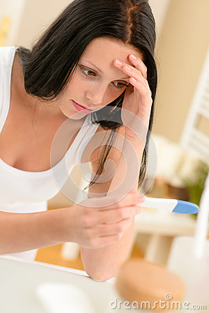 Frustrated woman positive pregnancy test result