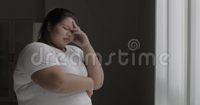 Frustrierte überladene Frau steht nahes Fenster stock footage