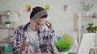 Frustrierter junger asiatischer Mann in einem Hemd gibt Daten mit einer Bankkarte auf einem Laptop ein stock video footage