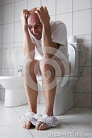 Frustrierter Mann auf Toilettensitz