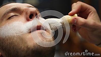 Fryzjer pracuje z pędzlem do golenia Zbliżenie człowieka, który uprząta mu brodę w barbershopie Piana biała zdjęcie wideo