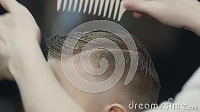 Fryzjer stawia włosy jego mały klient Chłopiec nowego ostrzyżenie Dziecka ostrzyżenie w zakładzie fryzjerskim zdjęcie wideo