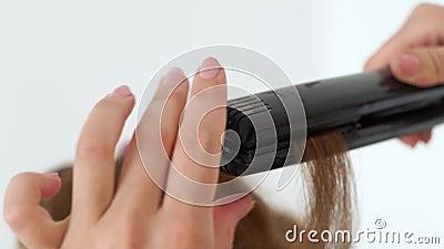Fryzjer używa włosianych tongs dla fryzować zakończenie up Proces fryzowanie długie włosy z żelazem w piękna studiu hairstylists zbiory wideo
