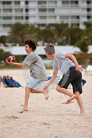 Teenage Boy Catches Ball In Beach Football Game Editorial Photo