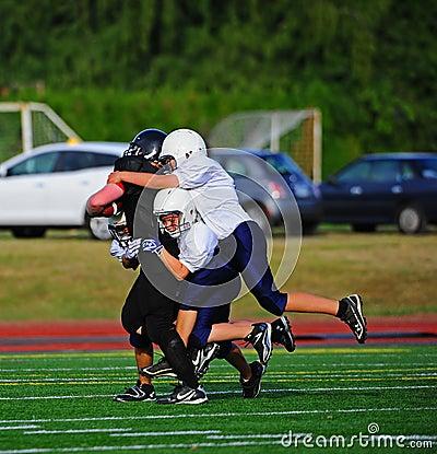 Fútbol americano de la juventud la toma abajo Foto editorial