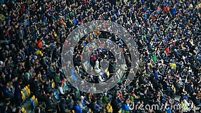 Fußballanhänger, die warme Kleidung, sitzend auf Tribünen tragen und Match aufpassen stock footage
