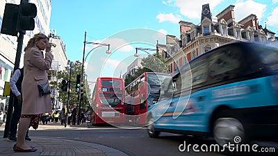Fußgängerüberquerung, Verkehr, Taxis und Doppeldeckerbusse in London Oxford Street, London, England stock video