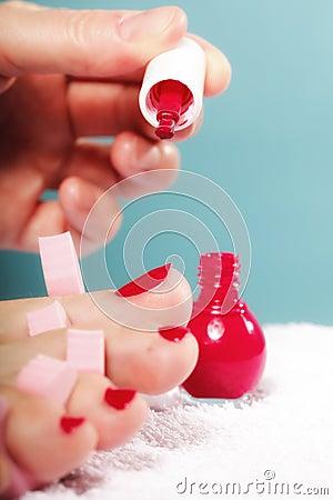 Fußpediküre welche die füße der frau mit den roten zehennägeln