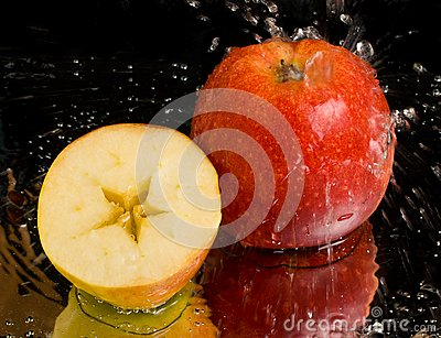 Full apple and half with water splashing