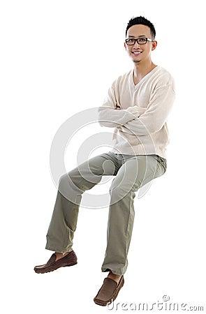 Full body Asian man sitting on a transparent block