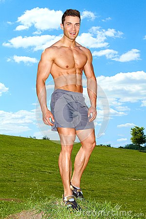 Full body of muscular man standing on grass