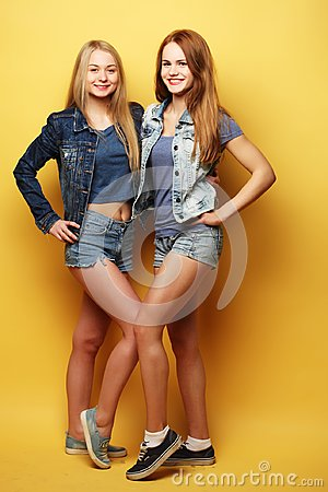 Free Full Body Portrait Of Two  Hipster Girls Over Yellow Background Royalty Free Stock Images - 99780089