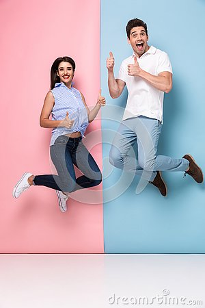 Free Full Length Image Of Cheerful Man And Woman In Casual Wear Jumping And Smiling Together, Isolated Over Colorful Background Royalty Free Stock Photo - 132152705