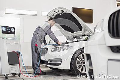Full length of male engineer examining car in automobile repair shop