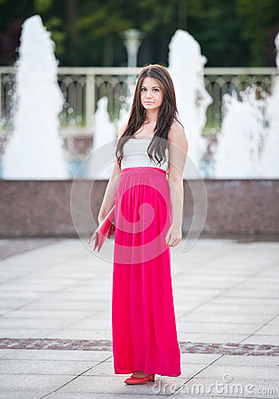 Free Full Length Of Young Caucasian Female With Long Red Skirt Standing In Front Of A Fountain Outdoor Stock Images - 32702504