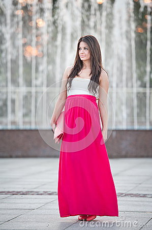 Free Full Length Of Young Caucasian Female With Long Red Skirt Standing In Front Of A Fountain Outdoor Stock Photography - 32702532