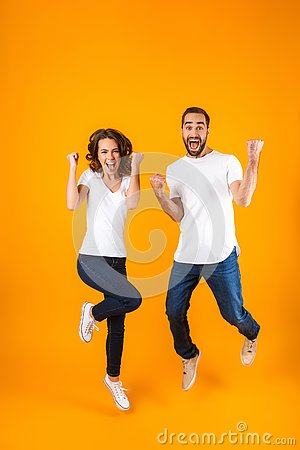 Free Full Length Photo Of Cheerful Couple Screaming In Surprise While Jumping, Isolated Over Yellow Background Stock Photography - 142524552