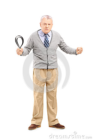 Full length portrait of an angry mature man holding a belt